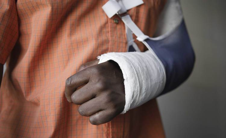 Injured person with arm in a cast and sling
