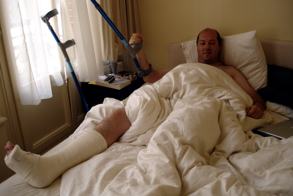 man in bed with crutches cannot work after auto accident