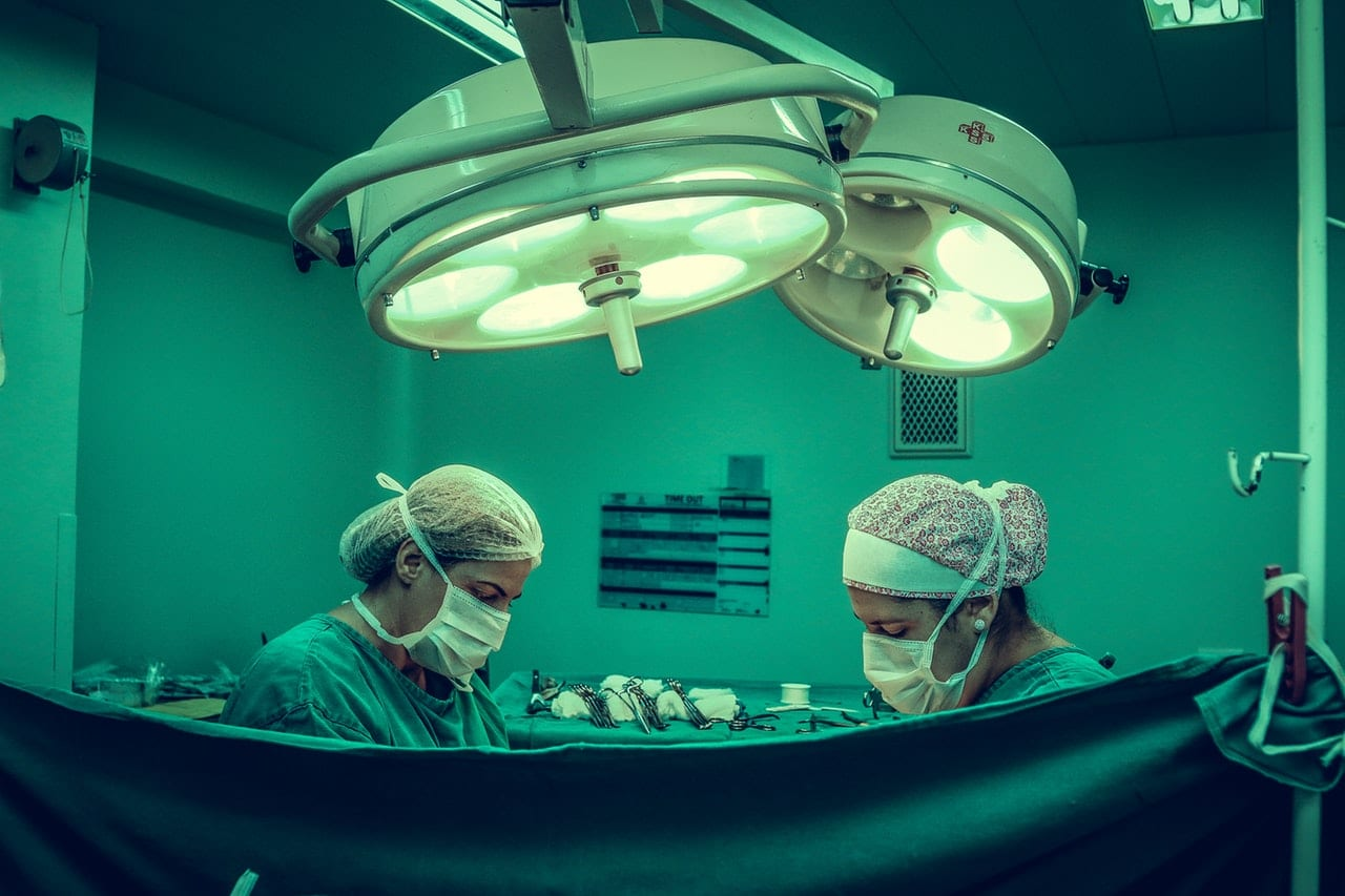 two doctors doing colorectal surgery behind curtain but not with defective hemorrhoid stapler
